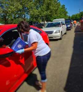 A volunteer handing out flyers to drivers