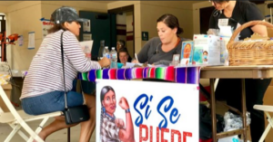 A woman at a relief goods table with volunteers